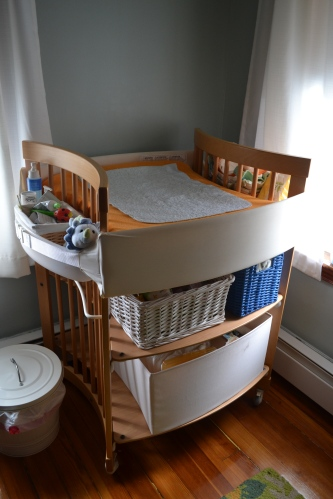 Most changing tables position the baby perpendicular to you, but this one is different as you can see. It usually comes with two canvas drawers. I cheaped out and got only one of the drawers and used baskets on the top shelf.