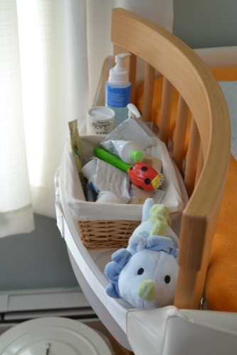 the left bin holds diaper cream, a brush and comb, lotion, and a toy — a must once your baby starts rolling over and needs distraction