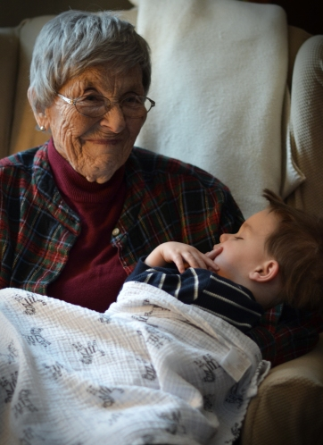 Grammy Alice holding a sleeping little boy.
